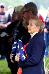 Retired supreme court justice Evelyn Stratton holds a flag presented to her by a military detail of one the remains of 11 service members who were given a military funeral at  at the Dayton National Cemetery June 30 ,2015. (Dispatch photo by Eric Albrecht)